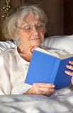 Elderly pensioner reading a book in bed Royalty Free Stock Images