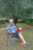 Elderly Pensioner Reading Book Garden. Smiling elderly pensioner having relax reading red book sitting on bench outdoor in the garden Royalty Free Stock Photography