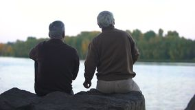 Elderly pensioners throwing stones in water, sitting on river bank, weekend rest. Stock footage stock video footage