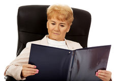 Elderly pensive focused business woman reading notes Stock Photo