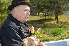Elderly pensive man with a bag of groceries Stock Photo