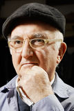Elderly pensive man in cap and eyeglasses Stock Photography