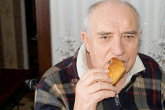 Elderly pensive man eating a bread roll Stock Photos