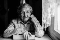 Elderly pensive woman with a book near the window. Elderly woman with a book near the window Stock Photo