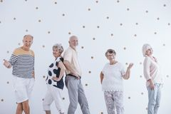 Elderly people celebrating new year`s eve against white wall wit. H gold dots royalty free stock photography