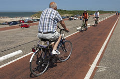 Elderly people cycling on Brouwersdam, Netherlands. The Brouwersdam, in the province Zealand,is a construction of the Delta Works, a series of construction Stock Images