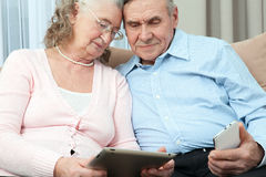 Elderly people. Elderly couple holding laptop, smartphone and make purchases over the Internet in the cozy living room of the hous Royalty Free Stock Images