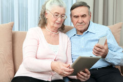 Elderly people. Elderly couple holding laptop, smartphone and make purchases over the Internet in the cozy living room of the hous Stock Photo