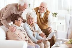 Elderly people enjoying modern technology. Group of elderly people enjoying modern technology in a retirement home stock photography