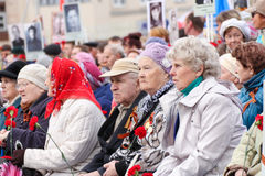 Elderly people with flowers at a rally. Royalty Free Stock Photography