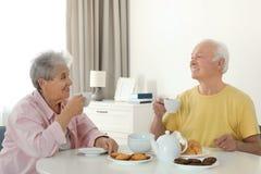 Elderly people having breakfast at nursing home royalty free stock images