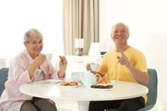 Elderly people having breakfast at nursing home stock photo