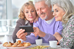 Elderly people having breakfast and using mobile phone Royalty Free Stock Images