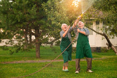 Elderly people having fun. Cheerful couple with garden hose Stock Images