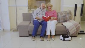 Elderly people hold book in hands and look in camera sitting on couch at home stock video footage