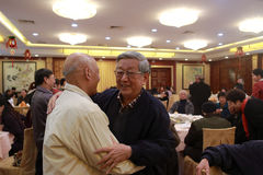 Elderly people hugging at the banquet in a restaurant Royalty Free Stock Image