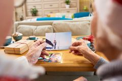Elderly People Looking at Photos. Back view of senior couple looking at family photographs remembering children during Christmas holidays royalty free stock photos
