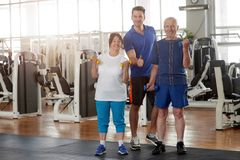 Elderly people with personal trainer at gym. Portrait of fitness trainer with senior couple showing thumb up. Healthy lifestyle for energy and longevity royalty free stock photos