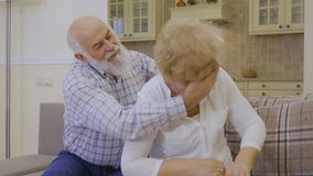 Elderly people quarrels at sofa at home. Senior man with senior woman sits on sofa at home and discussing something. Old couple are quarreling and man try to stock footage