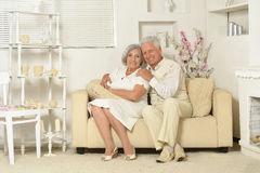 Elderly people sitting on couch. Two elderly people sitting at home on couch Royalty Free Stock Photo