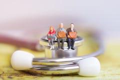 Elderly people sitting on stethoscope. Retirement planning. royalty free stock images