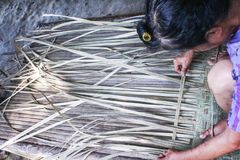 Elderly people sitting and weaving a reed mat , handmade  thai style royalty free stock photo