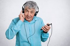 Elderly people and technology concept. Handsome grey haired male listens his favourite music in headphones, uses modern smart phon stock photo