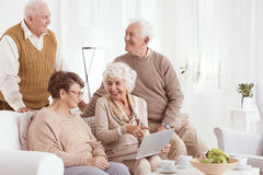 Elderly people and technology. Group of elderly people using new technology in retirement club Stock Image