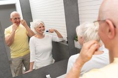 Old senior people cleaning teeth in the bathroom. Elderly people using brushing teeth and dental floss. Morning in the bathroom stock photo