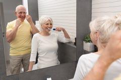 Old senior people cleaning teeth in the bathroom. Elderly people using brushing teeth and dental floss. Morning in the bathroom royalty free stock images