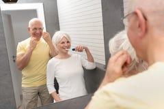 Old senior people cleaning teeth in the bathroom. Elderly people using brushing teeth and dental floss. Morning in the bathroom royalty free stock photos