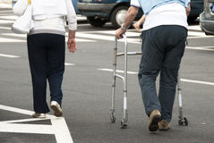 Elderly people walking. A elderly woman walking with her disabled husband royalty free stock photography