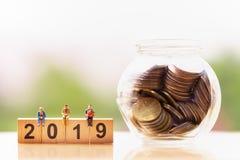 Elderly people and wood block word 2019 on nature background; money saving. stock photos
