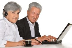 Elderly people working with laptop. Portrait of two elderly people working with laptop on white background Royalty Free Stock Photo