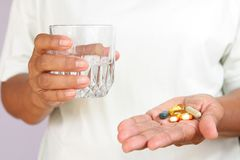 Patient holds a glass of water and medicine. stock photo