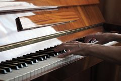 Elderly person hand playing the piano, close up royalty free stock image