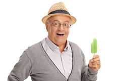 Elderly person holding a popsicle. Excited elderly person holding a green popsicle and looking at the camera isolated on white background Stock Images