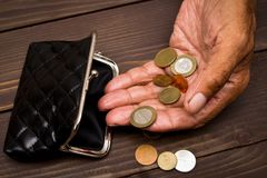 An elderly person holds the coins over the old empty wallet. The concept of poverty in retirement Stock Images