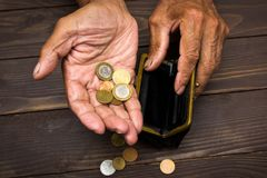 An elderly person holds the coins over the old empty wallet. The concept of poverty in retirement Royalty Free Stock Photos