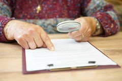 Elderly person with magnifying glass checking document Stock Image