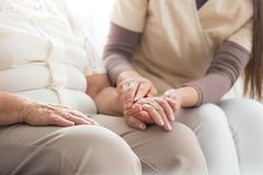 Elderly person with parkinson. Close-up of nurse taking care about elderly person with parkinson while sitting together at home royalty free stock images