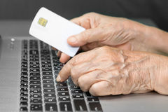 Elderly person using credit card for online shopping Stock Photography