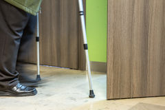 Elderly person using crutches entering opened door to see a doct Stock Photos