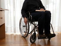Elderly person in a wheelchair reading a book Royalty Free Stock Photography