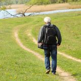 Elderly photographer with backpack. Goes to rural track distance Stock Images