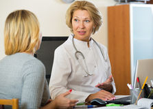 Elderly physician doing check up of sick female patient Stock Photos