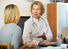 Elderly physician doing check up of sick female patient Royalty Free Stock Photo