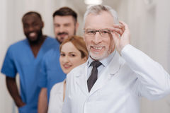 Elderly physician enjoying working responsibilities in the hospital Stock Images