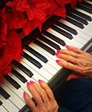 Elderly pianist. Photo of elderly woman playing a piano with red flower christmas decoration royalty free stock photography