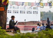 The elderly pilgrim reads mantras. The elderly pilgrim reads mantras touching beads, sitting under a tree against the background of the temple of the Maya Devi royalty free stock photos
